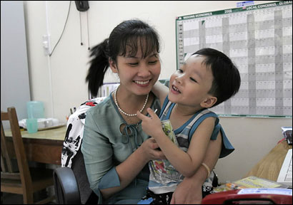 Pham Thi Hue, 26, an HIV patient at her office in Hai Phong, Vietnam with her 5-year-old son, Ha Minh Hieu.