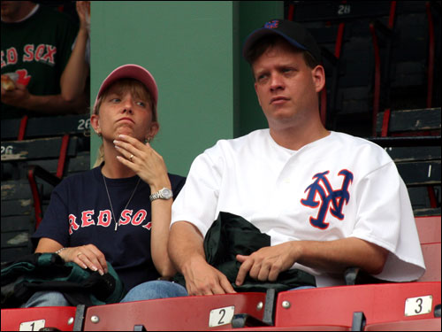 Sharon Miller, in a Red Sox shirt, is trying to convert Bill Busch, a longtime Mets fan originally from Old Bridge, NJ, now living in Medway. Bill's dad grew up a Dodgers fan, but since they relocated from Brooklyn to Los Angeles, Bill became a Mets fan. He predicted that the more strikeouts Pedro gets, the more the crowd would cheer.
