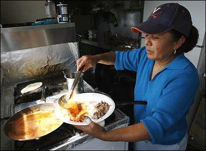 Tomasa Flores prepares lunch Wednesday, Aug. 16, at her family's food cart at the Jasper Wyman Blueberry Co. fields in Deblois, Maine. The Flores family provides meals to the migrant workers both at their cart and out in the field.