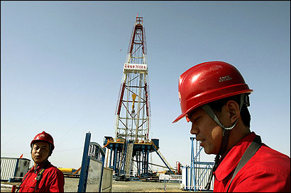 Workers stood near an oil and gas excavation well under construction in Lunnan in northwestern China last month.