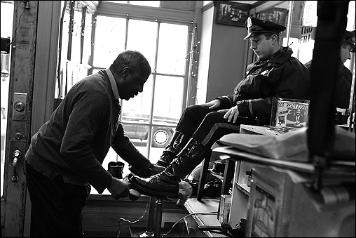BEACON HILL -- This is what $4 buys your feet at Beacon Hill Instant Shoe Repair: cleaning, application of wax or shoe cream (and possibly mink oil, suede protection, or saddle soap), buffing with a brush, buffing with a cloth, and edge dressing for the finishing touch. 'That's the finale,' says Ron Mills, who calls himself '009 Ronnie Shoeshine.' 'To keep a shine you have to get a shine.' Like other regulars, State Trooper Stephen Kavol visits Mills once a week to keep his boots in good condition. The shoe repair shop has been in this location across from the Statehouse on Bowdoin Street since 1906, according to its current owner, Vadim Kotlyar. That's a century of sole dedication to Boston's movers and shakers. (Globe Staff Photo / Suzanne Kreiter)