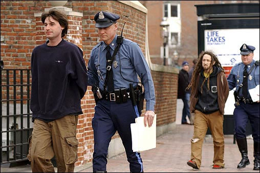 Sean Stevens (front) and Peter Berdovsky (rear) were escorted to their arraignment at the Charlestown District Court. The two artists were arrested last night following a publicity stunt gone awry. The two men are accused of plunging metropolitan Boston into a panic with illuminated advertisements for Aqua Teen Hunger Force, a late-night cartoon.