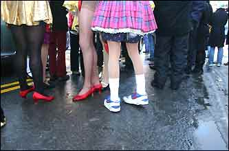 Bare legs and running shoes amid snow and slush at the parade.