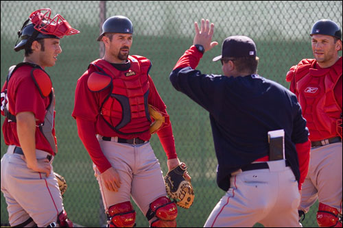 Catchers Kevin Cash (left), Jason Varitek, and Doug Mirabelli (right) get together with a member of the Sox coaching staff on Tuesday.
