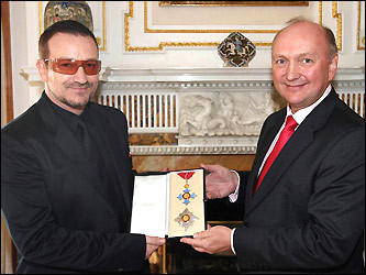 Bono (left) receives his honorary knighthood from British Ambassador David Reddaway (right)