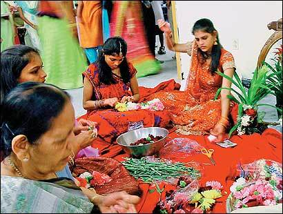 Women and girls make garlands for the gods for the inauguration of a temple in Lowell.