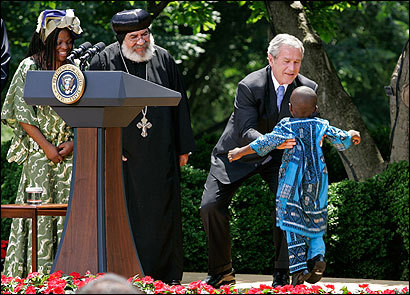 President Bush greeted 4-year-old Baron Mosima Looyios Tantoh of South Africa yesterday during a ceremony calling for a doubling of funding of the US global AIDS program to $30 billion over five years. The child, his HIV-positive mother, Manyonga (left), and Bishop Paul Yowakim of Kenya (center) have all been recipients of US funding for treating AIDS.