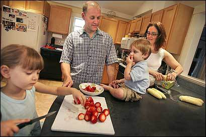 Marc and Amy Vachon prepare dinner with their children Maia, 5 (left), and Theo, 2, recently, Marc Vachon is among a group of dads redefining fatherhood, working with their spouses to carve out equality at home and at work so that parenting, career advancement, and all of life's rewards and challenges are shouldered and shared.