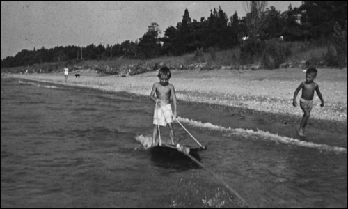 Young Mitt Romney ran along on the shore as his friend Tom McCaffrey went water skiing.