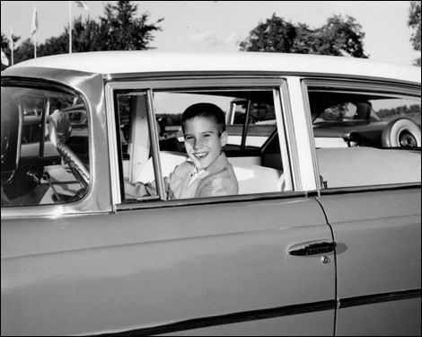 Mitt Romney, 11, behind the wheel of his father's Rambler.
