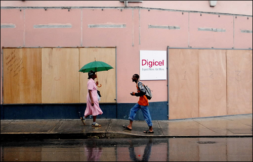 At left, Barbados residents walked past a boarded store in Bridgetown.