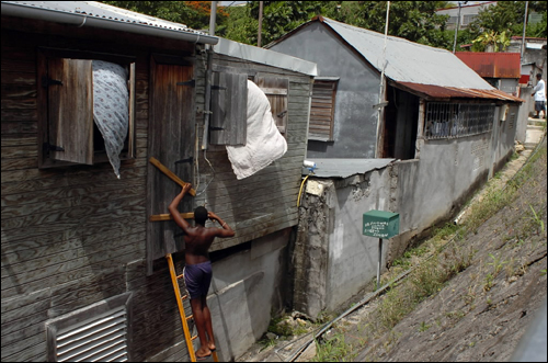Radio and television advisories urged people to stock up on canned food and fill their cars with gasoline, as hurricane warnings were in effect for the islands of St. Lucia, Martinique, Dominica and Guadeloupe. At left, a man prepared his house in Guadalupe.