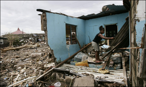 A resident removed debris from her home after Hurricane Dean passed the Bull Bay area in Kingston, Jamaica, on Monday.