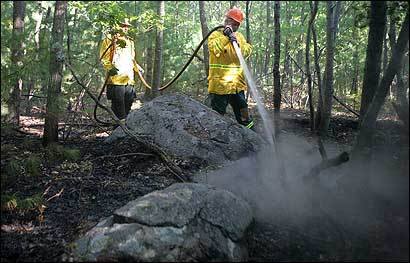 Ray Coutu of the Rochester Fire Department sprayed smoldering underbrush yesterday at Blue Hills Reservation.