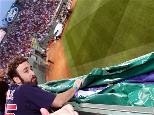 Adam Sack, originally from Newton, drove all the way from New York City to help lower the giant American flag over the wall at Fenway during the pregame ceremonies.