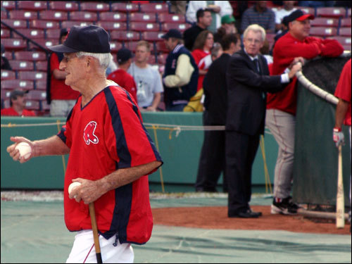 Red Sox legend Johnny Pesky who is completing his 55th season with the team, crossed the field to a greet a throng of cheering fans behind the dugout. ESPN's Peter Gammons and Angels manager Mike Scioscia looked on.