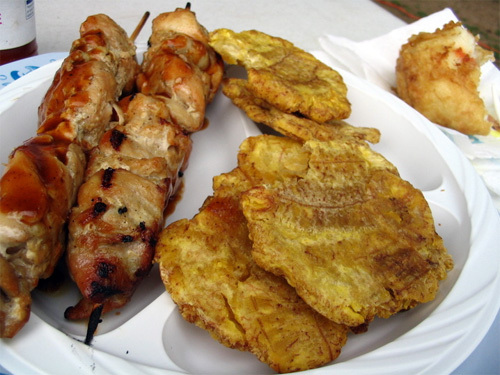 pinchos (skewers of bbq chicken) and tosotones (fried, salted plantains, like a side of fries in PR) and the remains of a relleno de patata (fried mashed potatoes stuffed with bbq chicken) in the back.