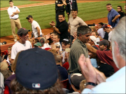 The Fenway faithful applauded as Danny Vinik (left) makes his way up the aisle for an impromptu interview with the media after his catch. In front of him is his father Jeff.