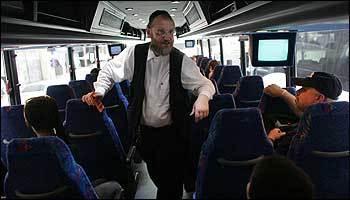 Vamoose president Zamuel Bluzenstein checks tickets on a bus before it departs Manhattan.