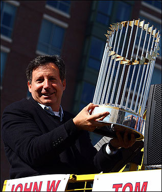 Sox Chairman Tom Werner holds the World Series trophy.