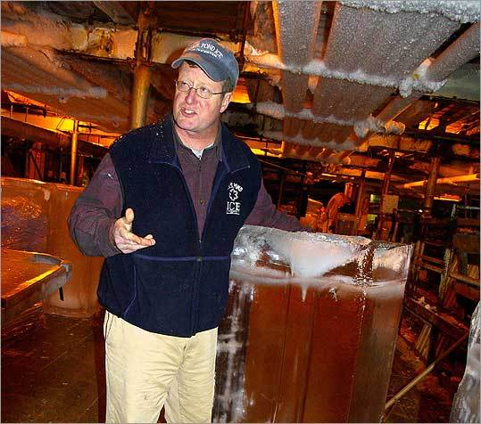 Scott Memhard, president of Cape Pond Ice in Gloucester, shows how easily a standard 335-pound block slides along the ice house floor.