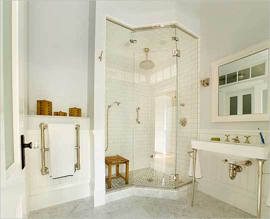 The corner shower, which doubles as a steam room thanks to floor-to-ceiling glass panels, is the focal point of the room.