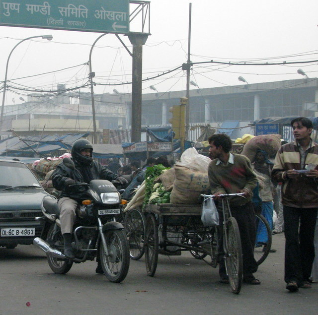 Motorcycles, vegetable vendors, cars, buses, auto rickshaws, and pedestrians compete for street space.