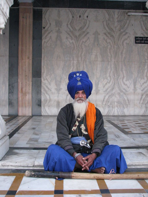 A Nahang Sikh at the guruwara. The medalion on his elaborate turban is the khanda, one of the five 'K's of Sikhism. He does not cut his hair or beard (kesh), and wears a comb called a kangha under his turban.