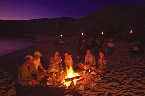 Roasting marshmallows over a campfire at twilight on Isla Carmen. STORY Sampling Baja PLAN Latin America travel guide
