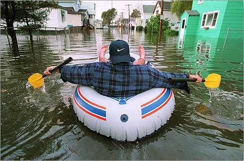 Massive destruction and disruptions have accompanied the many floods in New England over the past century. But the storms also brought out the strength in people who found unusual ways to cope. Here's a man paddling his way in an inflatable raft down Shawmut Street in Revere in October 1996.