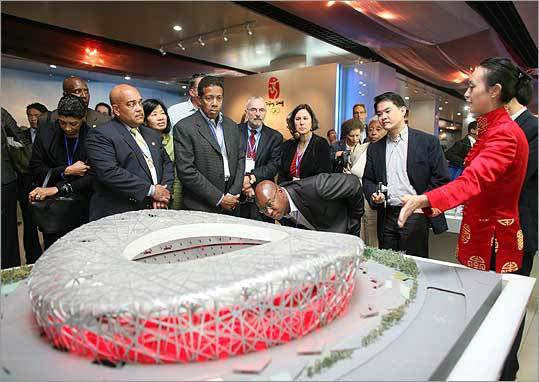 In Beijing, businessman Darryl Settles (eyeing model up close) and (from left, front row) John Hancock's Carol Fulp, Richard Walker of the Federal Reserve Bank, and entrepreneur Clayton Turnbull, as well as the BRA's Kairos Shen (right of Settles) check out a model of National Stadium, one of the sites for this year's Summer Olympics.