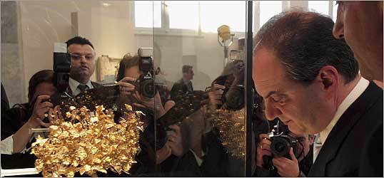 Top, Greek Prime Minister Costas Karamanlis with a gold Macedonian funerary wreath returned to Greece by the J. Paul Getty Museum in Los Angeles.