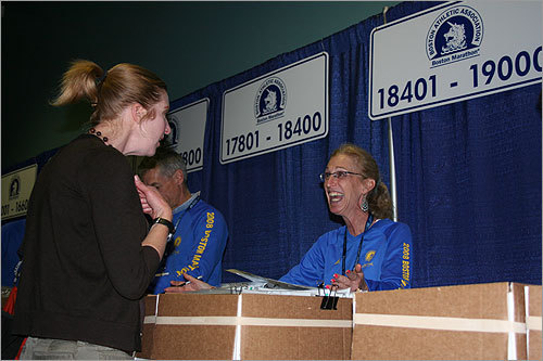 Volunteers, many of whom were employees of John Hancock, gave out bib numbers to runners.
