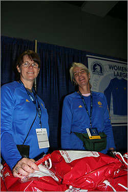 Volunteers Carol Bourque (left), 48, and Beezie Handy, 51, passed out shirts and other swag to runners. 'Everybody's happy and in a good mood,' Borque said. Both women have run the Boston Marathon once, although it's 'easier on the knees to volunteer,' Bourque said. Both modeled the new shirts tailored for women. 'It took them 112 years to make a women's shirt,' Borque said.