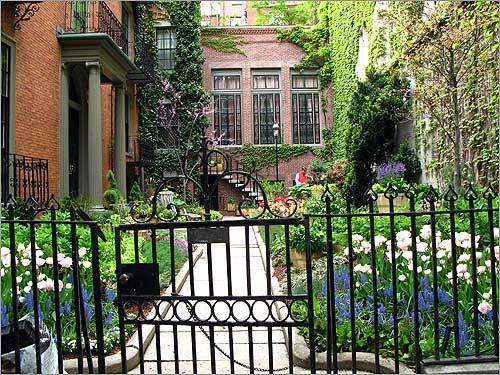 A garden gate in front of a colorful Beacon Hill garden.