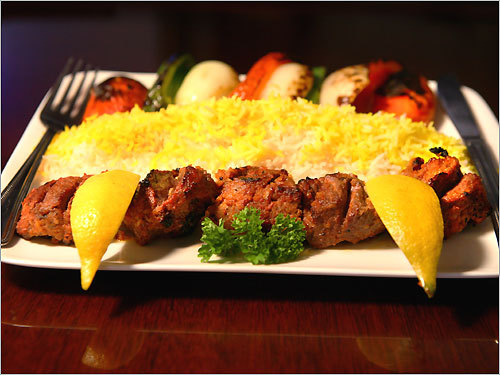 Shiraz Cuisine in Watertown serves lamb kebabs (above) with rice, lemon wedges, and grilled vegetables.