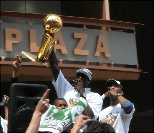 The Celtics' Kevin Garnett held the Larry O'Brien trophy high while backup point guard Sam Cassell smoked a cigar.