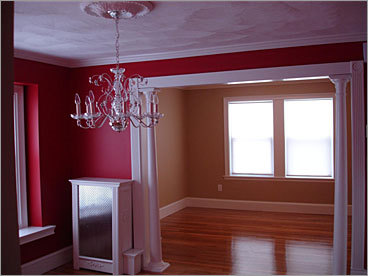 AFTER Location: Dining room Boulas painted the dining room a deep red, installed custom wainscoting and a Waterford chandelier. 'My intent was to create an elegant dining room,' he says.
