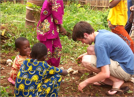 Chris McCarthy, a Northeastern University student, working with a couple of students at Honvie Primary School in Porto Novo, Benin.