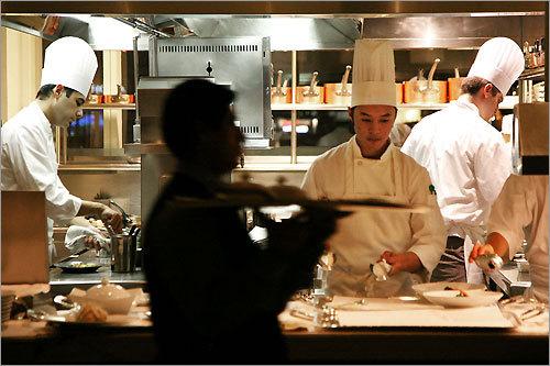 Chefs Arnold Marcella (center) and Cedric Vongerichten (left) prepare dishes in the open kitchen at Jean Georges.