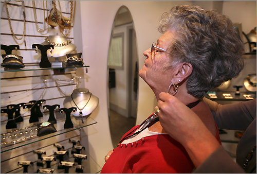 Gloria Finn, who was on a bus tour from Stark City, Mo., gets help with a necklace at High Gear Jewelry.