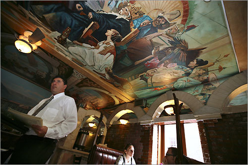 Anthony Gambale, a waiter at Lucia at 415 Hanover St., goes about his duties as tourists from Austria wait for their meal.