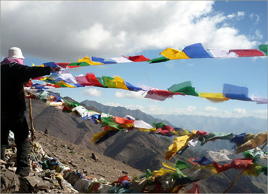 Gyaltsan Tsering, a guide, raises prayer flags atop Kongmaru La pass.