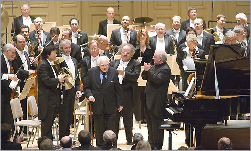 Elliott Carter, who turns 100 on December 11, is recognized on stage with BSO Music Director James Levine and pianist Daniel Barenboim after the world premiere of Carter's Interventions.