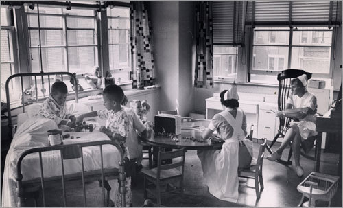 1960: Nurses observe children playing.