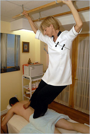 Julie Moore performs Ashiatsu Oriental Bar Therapy on a client in her Toronto studio. Ashiatsu therapists use wooden bars bolted into the ceiling or a portable apparatus with overhead bars to maneuver above their clients and to support a portion of their body weight as they vary the amount of pressure they apply with one foot, or sometimes both feet.