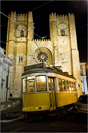One of Lisbon's signature yellow trolleys (also known as eléctricos) in front of the city's cathedral, known as the Sé de Lisboa.