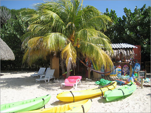 'A small beach in Curacao with floats and boats, just waiting for a casual loll on the aqua sea.'