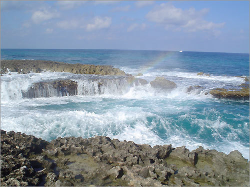 Rainbow formed by the spray of the waves crashing on the rocks in Aruba.