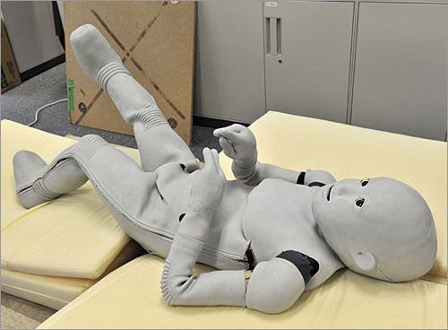 A 'Child-robot with Biomimetic Body,' or CB2, wriggles on a bed at Osaka University.